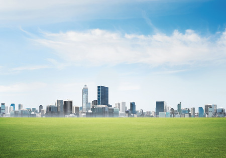 Photo pour Background image with modern cityscape blue sky and green spring field - image libre de droit