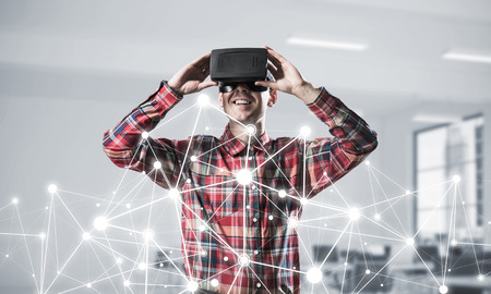 Photo for Young man with virtual reality headset or 3d glasses over connection background. Mixed media - Royalty Free Image
