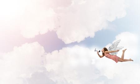 Foto de Young woman with megaphone flying high in sky - Imagen libre de derechos