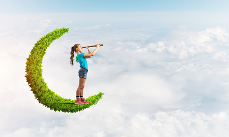 Photo for Cute kid girl on green moon in day sky looking in spyglass - Royalty Free Image