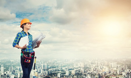 Photo for Engineer woman with blueprint on modern city landscape - Royalty Free Image