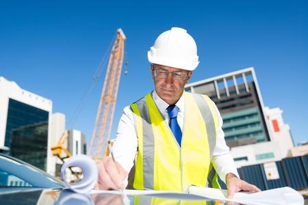 Foto de Engineer man in helmet and jacket controlling outdoor construction site - Imagen libre de derechos