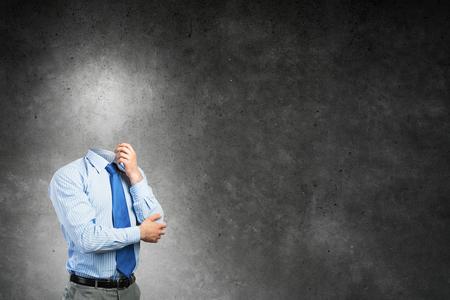 Photo pour Pensive businessman without head on concrete background - image libre de droit
