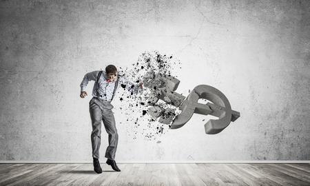Foto de Young furious businessman in empty room crashing with fist stone dollar symbol - Imagen libre de derechos