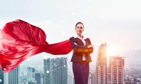 Photo pour Young confident businesswoman wearing red cape against modern city background - image libre de droit