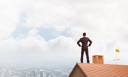 Foto de Young determined businessman standing on house roof and looking away. Mixed media - Imagen libre de derechos