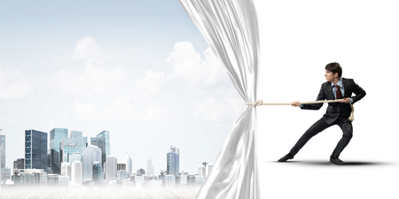 Foto de Businessman pulling white blank fabric. Place for text - Imagen libre de derechos