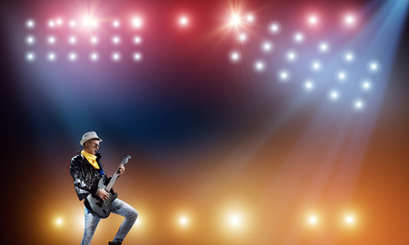 Photo for Young man rock musician in lights of stage - Royalty Free Image