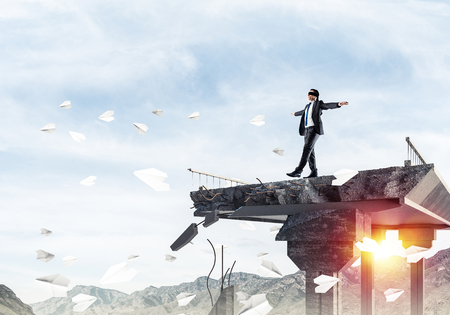 Foto de Businessman walking blindfolded among flying paper planes on concrete bridge with huge gap as symbol of hidden threats and risks. Skyscape and nature view on background. 3D rendering. - Imagen libre de derechos