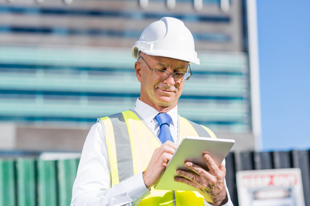 Foto de Senior engineer man in suit and helmet working on tablet pc - Imagen libre de derechos