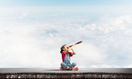 Photo pour Cute kid girl sitting on house roof and looking in spyglass - image libre de droit