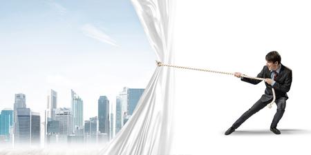 Photo pour Businessman pulling white blank fabric. Place for text - image libre de droit