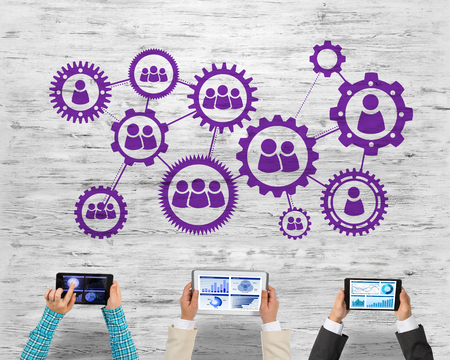 Foto de Group of three people with devices in hands working together as symbol of networking and communication - Imagen libre de derechos