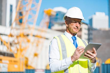 Foto de Senior engineer man in suit and helmet working on tablet pc - Imagen libre de derechos