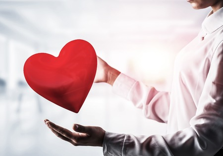 Photo pour Cropped image of business woman in shirt keeping big red heart in his hands with office view and sunlight on background. Mixed media. - image libre de droit