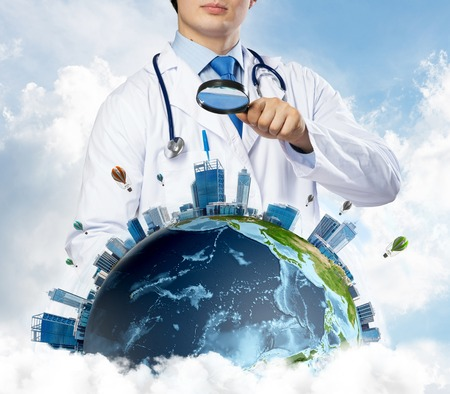 Foto per Conceptual image of confident doctor in white medical uniform looking on the Earth globe through loupe with cloudy skyscape on background. Medical industry concept. - Immagine Royalty Free