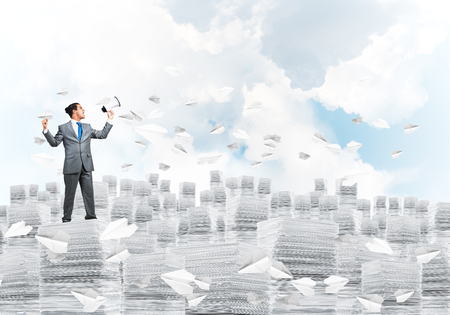 Photo pour Businessman in suit standing on pile of documents among flying paper planes with speaker in hand with cloudly skyscape on background. Mixed media. - image libre de droit