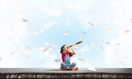 Photo for Cute kid girl sitting on house roof and looking in spyglass - Royalty Free Image
