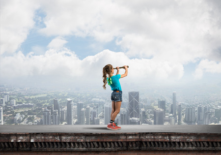 Photo for Cute kid girl standing on house roof and looking in spyglass - Royalty Free Image