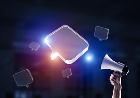 Photo pour Male hand holding megaphone with glass empty speech bubbles in air. Mixed media - image libre de droit