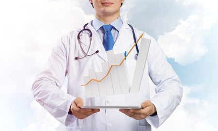 Foto de Young doctor in sterile medical suit presenting tablet with graphical chart in hands while standing against cloudy skyscape view on background. - Imagen libre de derechos