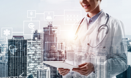 Foto de Cropped image of confident medical industry employee standing outdoors and holding tablet in hands. Young female doctor using tablet. Double exposure with medical interface icons - Imagen libre de derechos