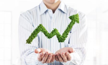 Foto de Palms of businessman in suit presenting green plant in form of growing graph. Mixed media - Imagen libre de derechos