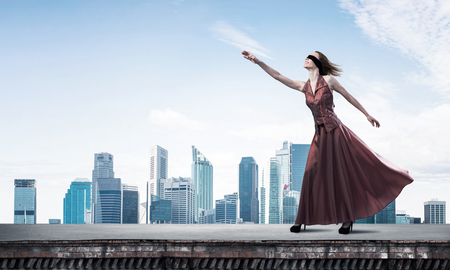 Foto de Young attractive woman wearing blindfold and stretching hand against cityscape background - Imagen libre de derechos