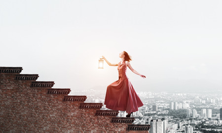 Photo for Young attractive woman in red dress with lantern walking up staircase. Mixed media - Royalty Free Image