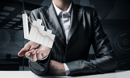 Foto de Cropped image of businessman in suit presenting growing graph in his hand with dark office view on background. 3D rendering. - Imagen libre de derechos