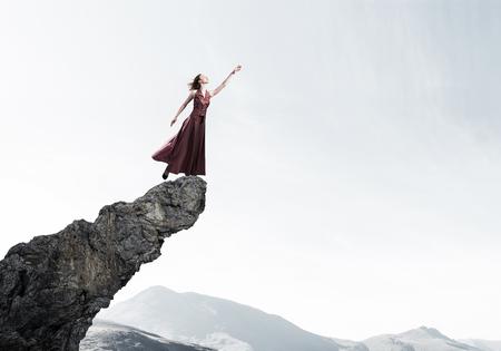 Foto de Young attractive woman relaxing in summer day standing on rock top - Imagen libre de derechos