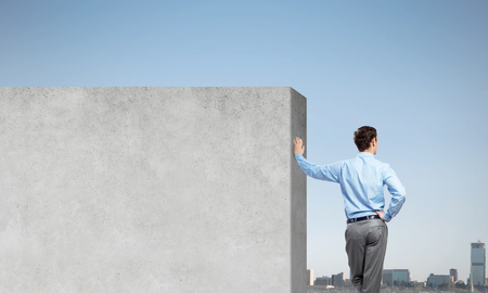 Photo for Businessman standing with back and leaning on cement blank wall - Royalty Free Image