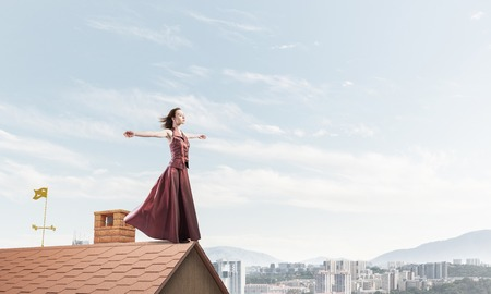 Foto de Young attractive woman on brick house roof stretching hand to sky. Mixed media - Imagen libre de derechos