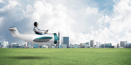 Photo for Young aviator driving small propeller plane. Modern metropolis with high buildings on background. Man in airplane flying low above ground. Dreaming and imagination mixed media concept. - Royalty Free Image