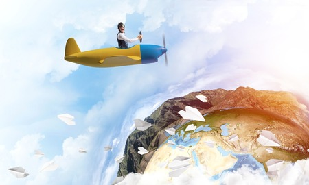 Photo pour Pilot in leather helmet driving propeller plane on background of blue cloudy sky. Traveling around the world by airplane. Funny man flying in small airplane. Earth horizon with high mountain range - image libre de droit
