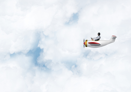 Foto de Man in aviator hat with goggles driving propeller plane. Funny man having fun in small airplane. Blue cloudy sky with fluffy clouds. Businessman sitting in paper plane and holding steering wheel. - Imagen libre de derechos