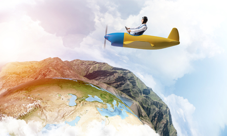 Photo pour Happy pilot driving small propeller plane on background of blue sky with clouds. Traveling around the world by airplane. Funny man flying in small airplane. Round earth with mountain landscape. - image libre de droit
