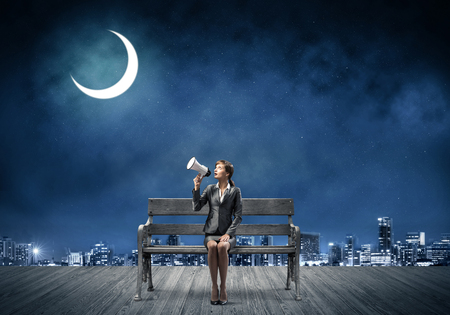 Photo pour Business woman with megaphone sitting on wooden bench. Female speaker shouting in loudspeaker outdoors. Modern cityscape panorama at night. Business marketing and announcement. - image libre de droit