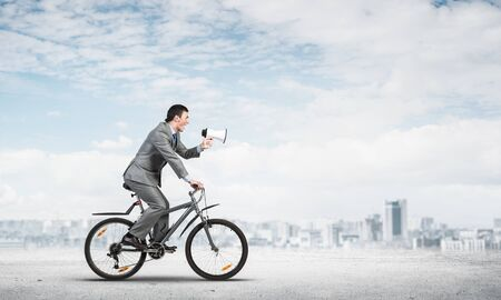 Photo pour Businessman with megaphone on bike at sunny day. Marketing and advertising campaign. Manager in business suit riding bicycle on road. Male cyclist on background of blue sky and city on horizon - image libre de droit