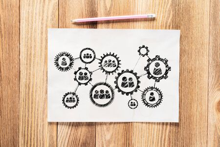 Foto de Business process management pencil hand drawn with group of rotating cogwheels. Human resources sketch on wooden desk. Workplace with paper and pencil on wooden desk. Social communication infographics - Imagen libre de derechos