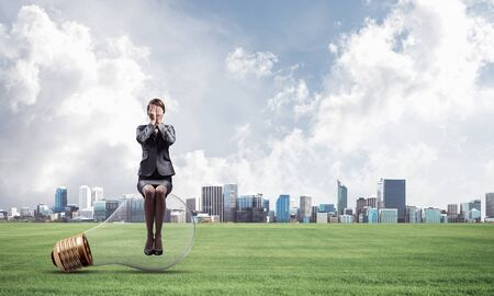 Photo for Young woman sitting on big light bulb. Girl in business suit keeps hands on face for surprise. Businesswoman playing hide and seek on background of modern downtown. Problem and successful solution - Royalty Free Image