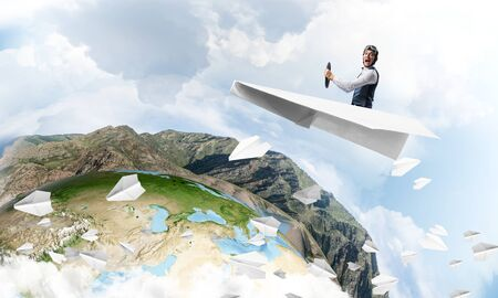Photo pour Pilot in leather helmet and goggles driving paper plane on background of blue cloudy sky. Traveling around the world. Funny man flying in small paper airplane. Earth horizon with high mountain range - image libre de droit