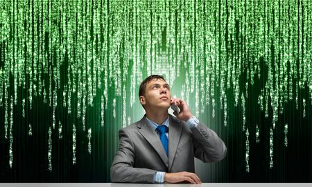 Photo for Young man talking on phone and looking upward. Businessman sitting at desk on background abstract binary code chain. Portrait of guy wears business suit and tie. Deep cyberspace and virtual network - Royalty Free Image