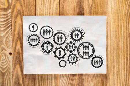 Foto de Corporate social responsibility concept with group of rotating gears and cogs. Human resources cooperation sketch on wooden surface. Workplace with sheet of paper lying on wooden desk. - Imagen libre de derechos