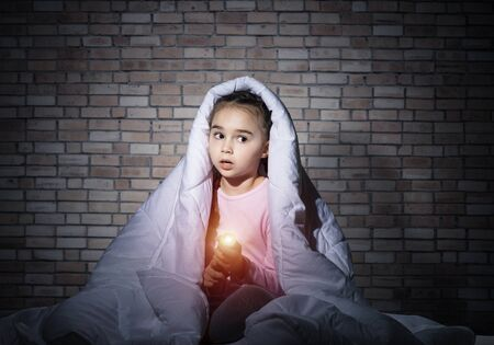 Foto de Frightened girl with flashlight hiding under blanket. Scared kid lying in his bed at home. Night terrors of child. Little girl afraid of dark. Child in pajamas on background of grey wall. - Imagen libre de derechos