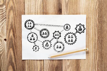 Foto de Corporate HR management pencil hand drawn with group of rotating gears and cogs. Business team building sketch on wooden surface. Top view of workplace with paper and pencil lying on wooden desk. - Imagen libre de derechos