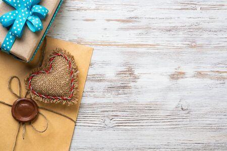 Photo for Flat lay cute composition with handmade fabric heart. Gift box and retro mail envelope on wooden table. Happy birthday or anniversary congratulation. Romantic love story template with copy space. - Royalty Free Image