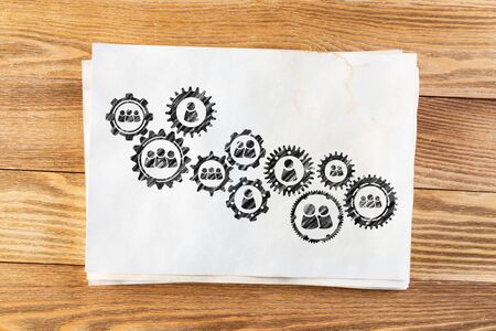 Foto de Business process management pencil hand drawn with group of rotating cogwheels. Human resources sketch on wooden desk. Workplace with sheet of paper on wooden desk. Social communication infographics - Imagen libre de derechos