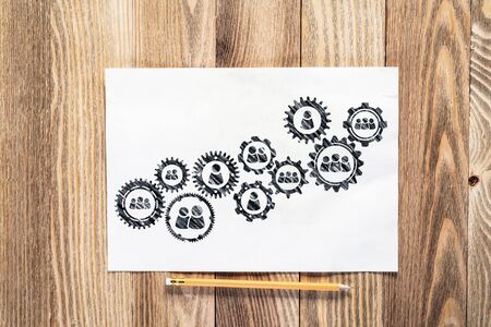 Foto de Human resource recruitment pencil hand drawn with group of rotating cogwheels. Headhunting and team building sketch on wooden surface. Top view of workplace with paper and pencil lying on wooden desk. - Imagen libre de derechos