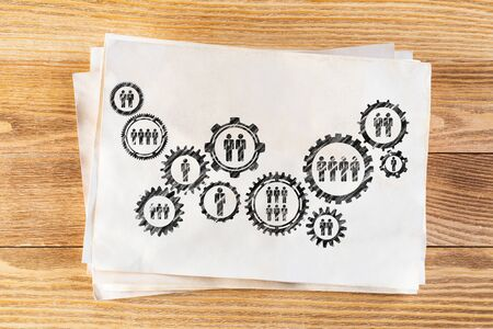 Foto de Corporate social responsibility concept with group of rotating gears and cogs. Human resources cooperation sketch on wooden surface. Workplace with paper stack lying on wooden desk. - Imagen libre de derechos